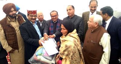 DyCM Dr Nirmal Singh giving relief material to a beneficiary at Jallandhar on Sunday.