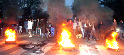 Protesters blocking road near main gate of Jammu University on Friday — Excelsior/Rakesh