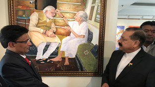 "Union Minister Dr Jitendra Singh going around the paintings on display at an exhibition by Udhampur-based ""Foot Artist"" Uttam Kumar Bharadwaj, at Chanakyapuri, New Delhi on Monday."