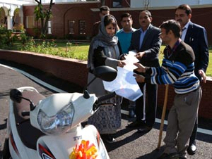 Chief Minister Mehbooba Mufti handing over a key of motorised scooter to handicapped person at Jammu.