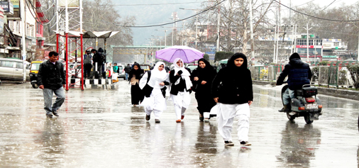 Umbrellas out in Srinagar as Kashmir valley experienced torrential rains disrupting normal life on Wednesday. (UNI)