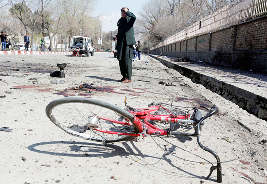 An Afghan man inspects the site of a suicide attack in Kabul, Afghanistan on Wednesday.
