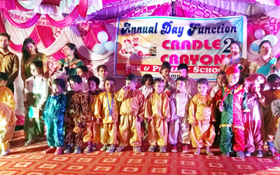 Children in colourful attires posing for a group photograph at Cradle 2 Crayons School in Jammu.