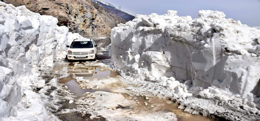 A vehicle moves on snow bound Mughal road on Monday. -Excelsior/Younis Khaliq
