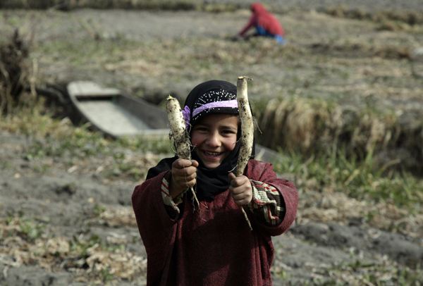 A girl poses for a picture as she holds Radish in a vegetable garden in Srinagar. -Excelsior/Shakeel