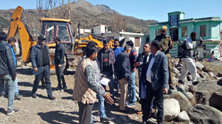 A JCB demolishing illegal structures raised on Govt land at Koteranka.