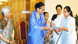 First Lady Usha Vohra presenting certificate to a girl on completion of basic computer course.