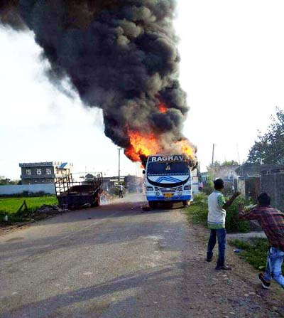 A bus carrying baratis in flames at Dolian Jattan in Hiranagar on Tuesday. —Excelsior/Madan