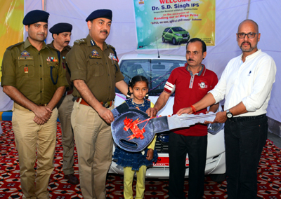 Dr SD Singh, IGP, Jammu Zone, alongwith Rajesh Sharma, Retail Territory Manager of BPCL in J&K handing over key of a car to its winner during a customer connect programme of BPCL at Kathua.