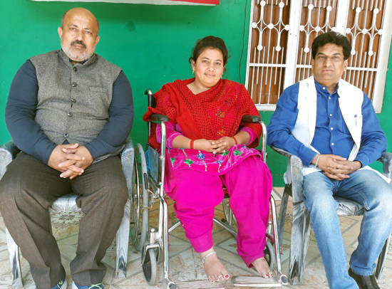 SC, ST, BC, Corporation VC, Balbir Ram Rattan posing with a firing victim after handing over wheel chair to her in village Chachwal in Samba on Thursday.