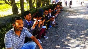 Voters take rest in a long queue as they wait for their turn to cast votes for the LAHDC Kargil on Monday.