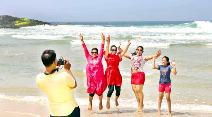 A group of tourists enjoying themselves at Kovalam beach in Thiruvananthapuram on Friday. (UNI)