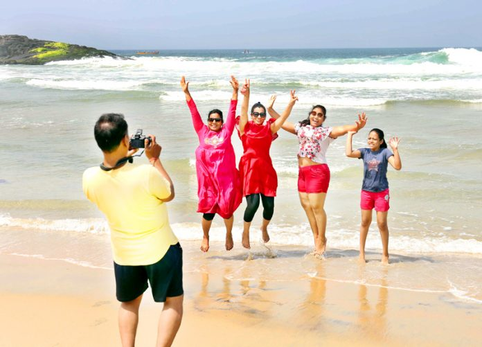 A group of tourists enjoying themselves at Kovalam beach in Thiruvananthapuram on Friday. (UNI)