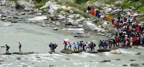Stranded passengers moving through a Nallah at Magarkote to catch a vehicle to reach their destinations in view of blocked highway on Sunday morning.