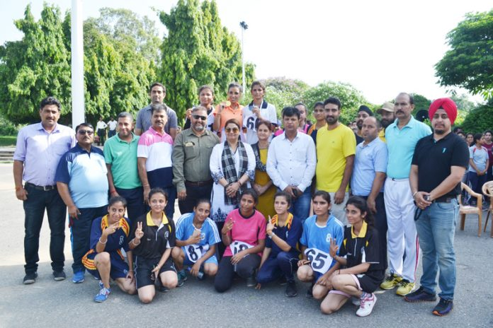 Women Athletes posing along with digniatries with officials after Cross Country organised by JU.