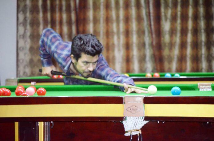 Cueist Miya Bashir aiming at target during a match of Srinagar District Sr Snooker Championship in Srinagar.