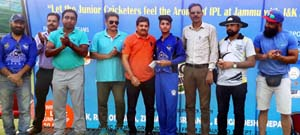 Man of the match winner posing with coaches and umpires.