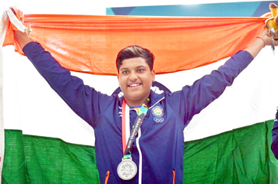 Young shooter Shardul Vihan holding National Flag after winning Silver Medal in Asian Games.