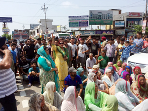 Residents raising slogans during protest at Karan Bagh near Satwari, Jammu on Saturday.