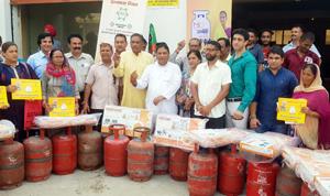 MLA Jammu West Sat Sharma distributing LPG connections at Shanti Nagar on Thursday.