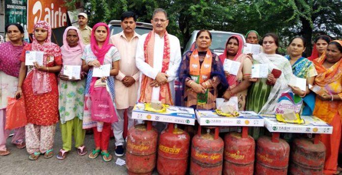 MLA Gandhi Nagar and former Deputy CM, Kavinder Gupta distributing LPG connections at Gandhi Nagar on Friday.