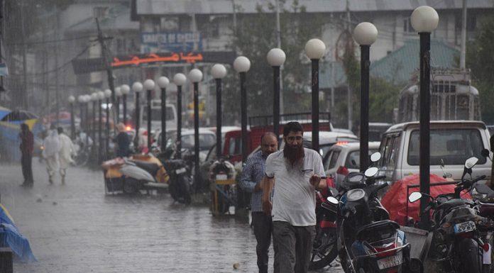People walk amid heavy rains in Srinagar on Thursday. —Excelsior/Shakeel