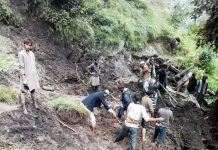 Locals clearing the debris to retrieve the dead bodies in Gandoh, Doda on Monday. -Excelsior/Rafi Choudhary