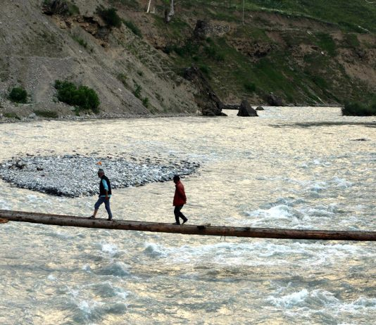 People use a temporary bridge built to cross the river in famous tourist resort of Sonamarg. -Excelsior/Shakeel