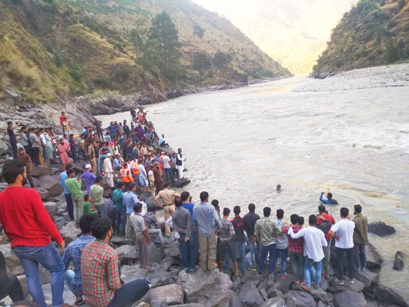 People trying to fish out the body of a deceased Government teacher from river Chenab. —Excelsior/Rafi Choudhary