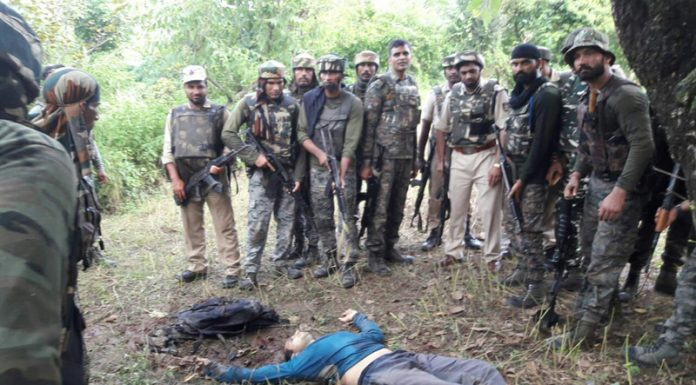 Security personnel stand around the body of slain militant at village Dirthi in Kakryal area on Thursday. —Excelsior/Rakesh