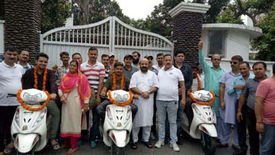 MLA Raipur-Domana, Bali Bhagat, posing with differently abled persons after handing over scooties to them.