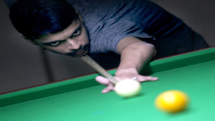 A cueist aiming at target during 26th Billiards and Snooker Championship at Billiards Hall, MA Stadium in Jammu on Wednesday. -Excelsior/Rakesh