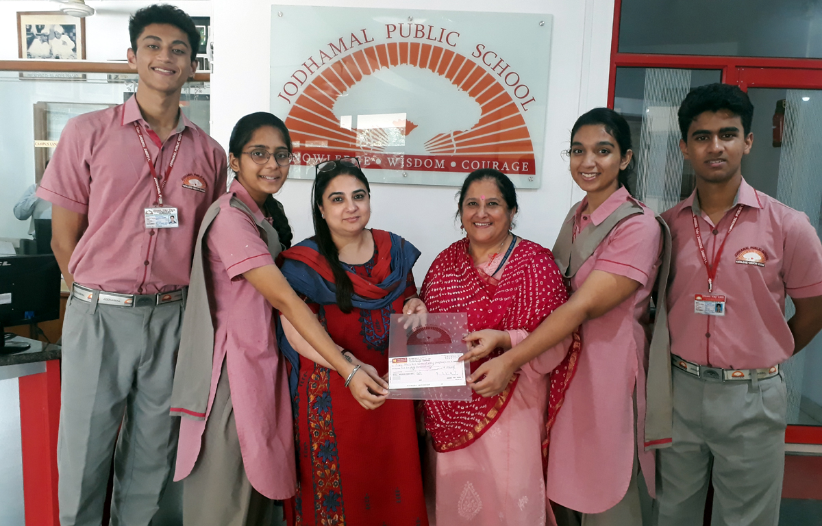 Students presenting a draft of Rs 2.5 lakh to Director of Jodhamal Public School on Monday.
