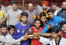 Martial Art players holding shield while posing for a group photograph along with dignitaries in Budgam.