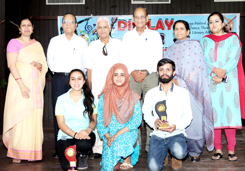Winners of JU's Display Your Talent holding trophies while posing for a photograph along with dignitaries.