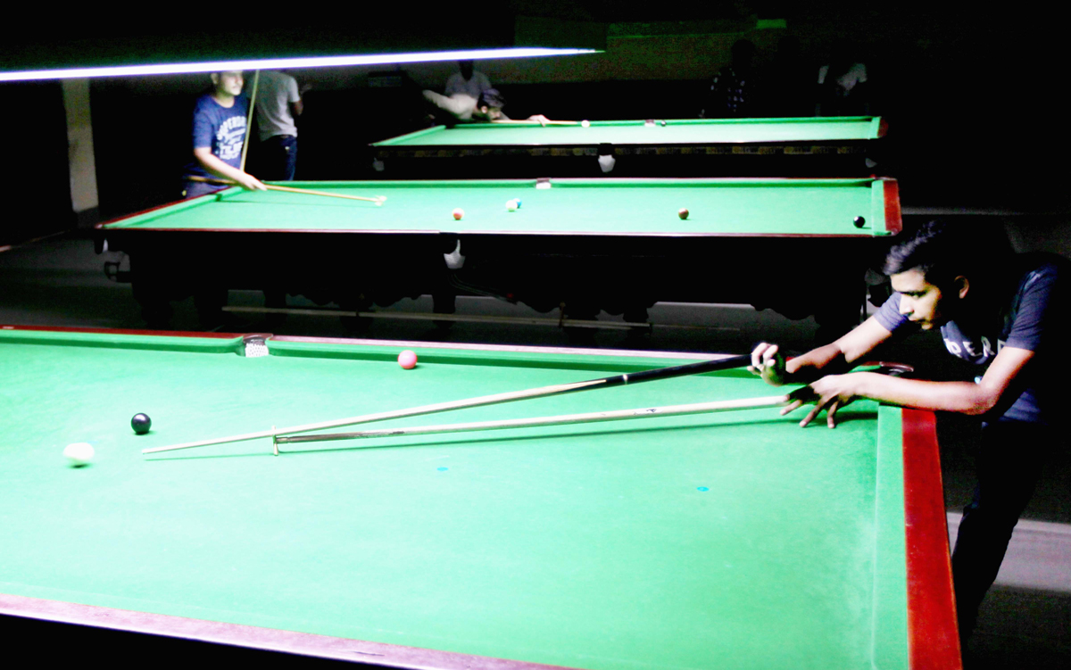 Cueist aiming at target in Junior Snooker Championship at Billiards Hall, MA Stadium in Jammu. -Excelsior/Rakesh
