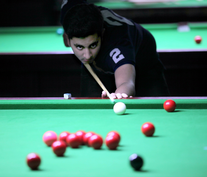 Cueist Abhirath Gulati in action during a match of Junior Snooker Championship at Billiards Hall, MA Stadium in Jammu. -Excelsior/Rakesh