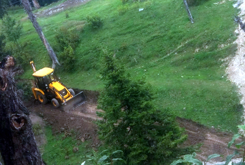 Earth mover cutting a road illegally through forest area in Gulmarg. -Excelsior/Aabid Nabi.