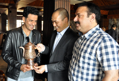 Secretary Tourism, Rigzin Samphel and Director Tourism Kashmir, Tasaduq Jeelani presenting special traditional tea pot to Bollywood Actor/Director Manoj Bajpayee at Srinagar on Wednesday.