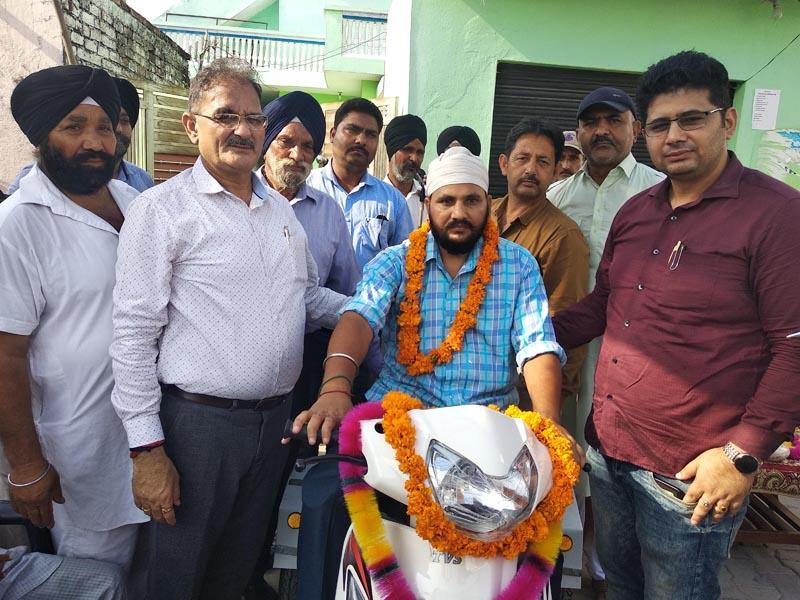 MLA Gandhi Nagar, Kavinder Gupta posing with a handicapped man after handing over a tri-scooter to him.