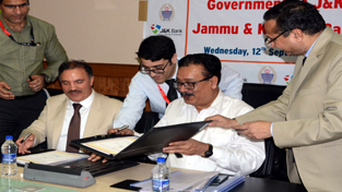 Principal Secretary, Finance, Navin Kumar Choudhary and Chairman & CEO, J&K Bank, Parvez Ahmad, signing MoU at Srinagar on Wednesday.