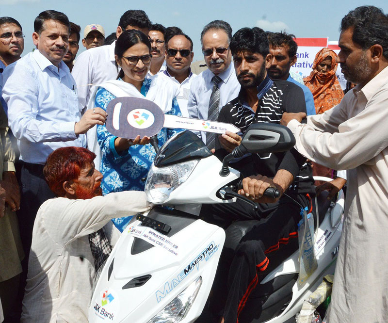 Deputy Commissioner, Sushma Chauhan giving away scooty to a specially-abled member from a nomadic family in Samba on Tuesday.
