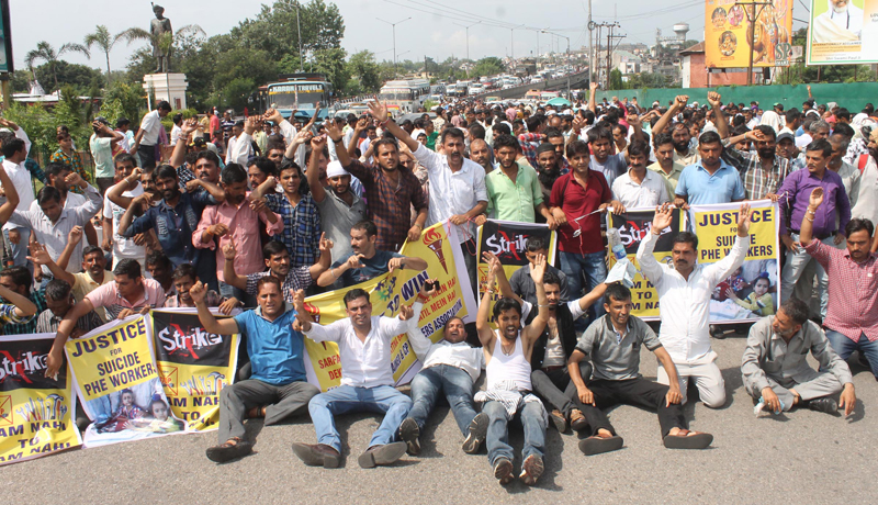 PHE workers staging protest near Tawi bridge in Jammu on Friday. -Excelsior/Rakesh