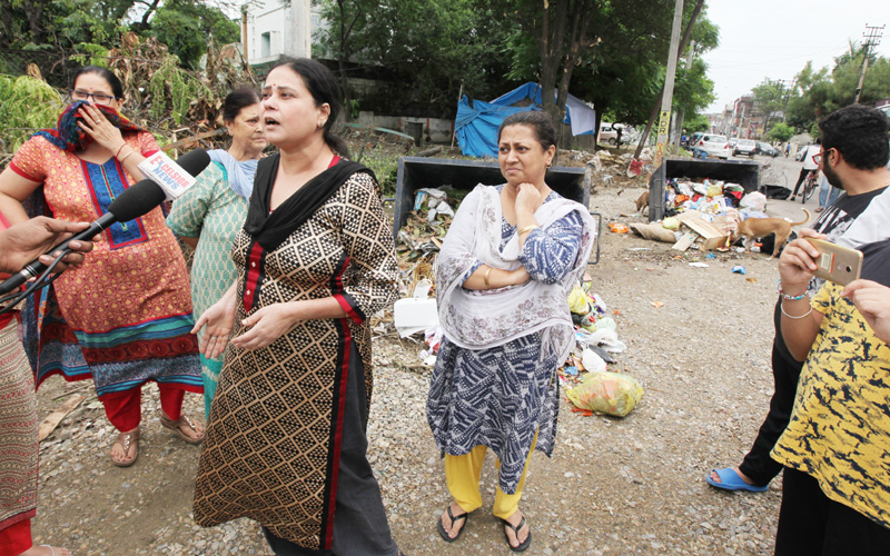 A lady narrating the ordeal regarding the dumping of garbage near Valmiki Chowk in Gandhi Nagar area of Jammu. -Excelsior/Rakesh