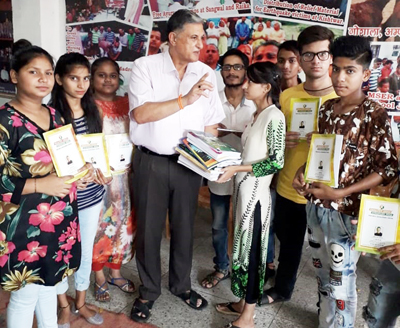 Chairman of NGO 'Healthy India Stronger India', Hira Lal Abrol distributing notebooks among the poor students in Jammu on Tuesday.