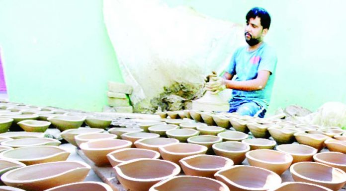 A worker prepares earthen lamps ahead of Diwali festival in Jammu. —Excelsior/Rakesh