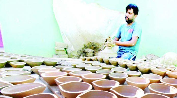 A worker prepares earthen lamps ahead of Diwali festival in Jammu. —Excelsior/Rakesh