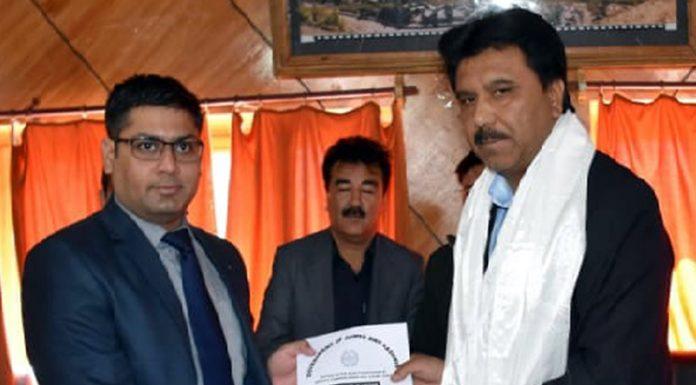 DC Kargil Vikas Kundal handing over letter of election to Feroz Khan in Kargil on Monday.