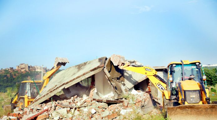 A JCB demolishing 'Pucca' house during anti-encroachment drive at Sidhra in Jammu on Monday. -Excelsior/Rakesh