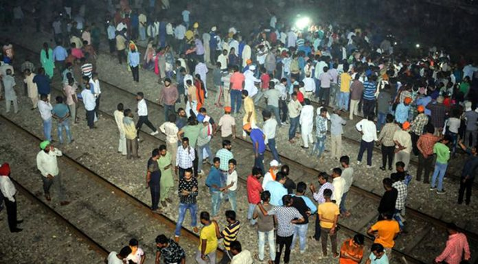 People gather near the site of a train accident at Joda Phatak in Amritsar on Friday.